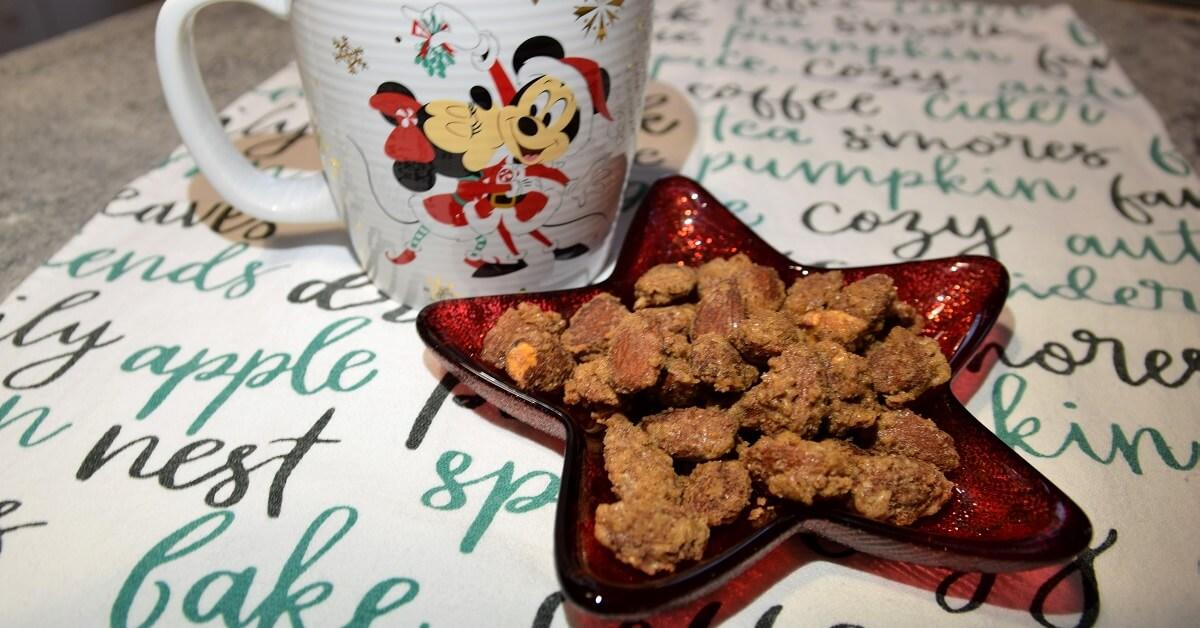 Die fertig zubereiteten Glazed Almonds nach Disney World Rezept liegen in einer sternförmigen Schale neben der eine Tasse mit weihnachtlichem Disneymotiv zu sehen ist