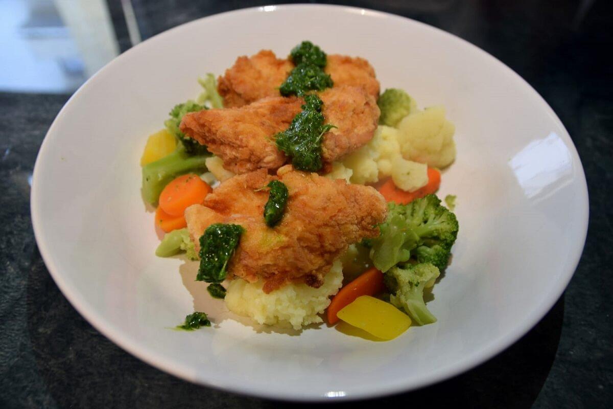 Auf einem großen Teller ist eine Portion des Fried Endorian Tip Yips mit Kartoffelstampf, Gemüse und Kräutersoße angerichtet
