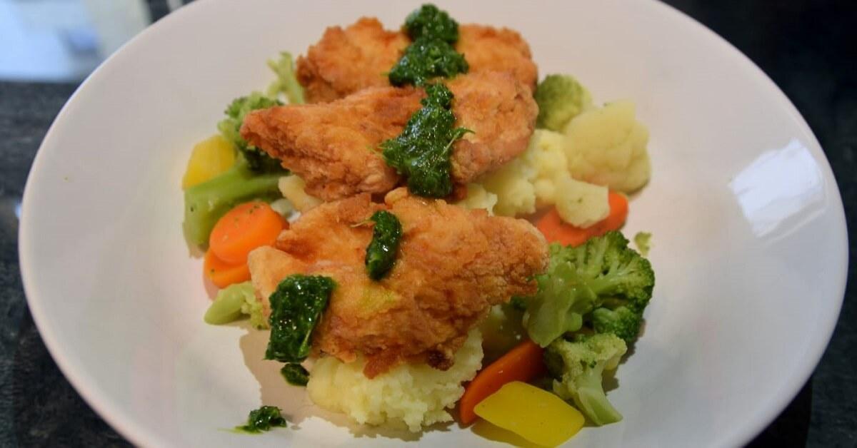 Auf einem großen weißen Teller ist eine Portion des Fried Endorian Tip Yips mit Kartoffelstampf, Gemüse und Kräutersoße angerichtet