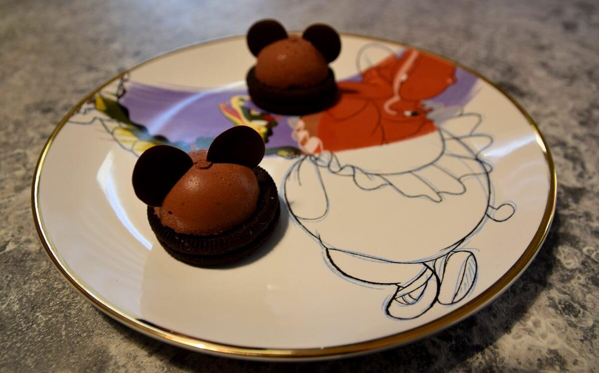 Zwei Mickey Mousse Domes liegen auf einem Teller mit Fantasia-Motiv