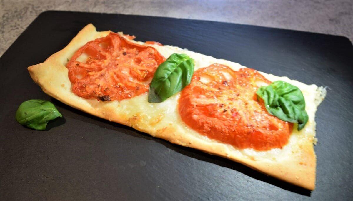 Auf einer Schieferplatte ist ein Stück des Oven Dried Tomato Flatbreads mit Basilikum angerichtet
