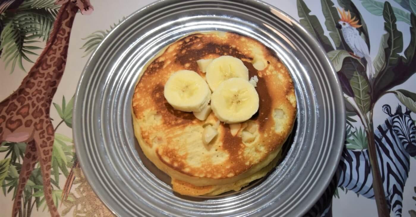 Auf einem grauen Teller liegt ein Stapel von Pancakes mit Macadamianüssen und Bananenscheiben obenauf