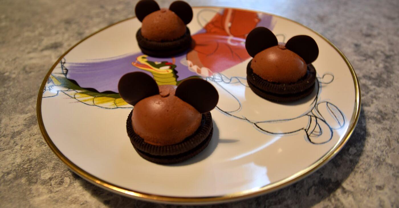 Auf einem Teller mit Fantasia-Motiv liegen drei Mickey Mousse Domes nach einem Rezept aus dem Chef Mickey's in Walt Disney World