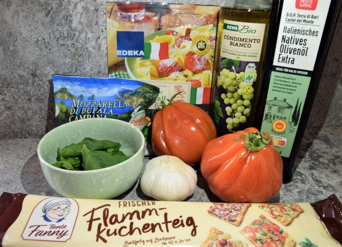 Auf einer Küchenarbeitsfläche liegen mehrere für das Oven Dried Tomato Flatbread benötigte Zutaten