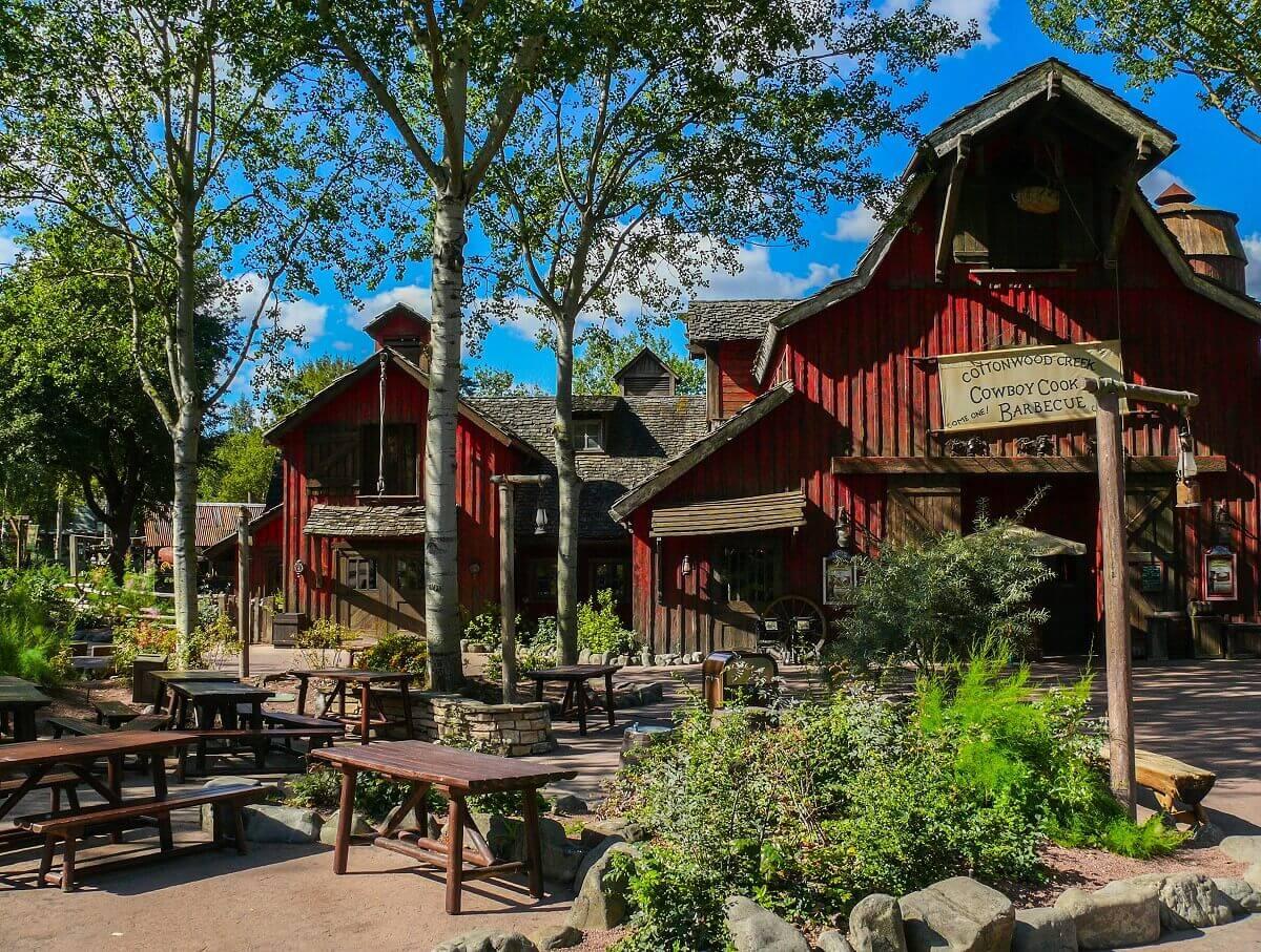 Im Hintergrund das Restaurant Cowboy Cookout Barbecue, davor einige Sitzbänke mit Tischen zwischen Bäumen und Sträuchern.