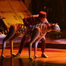 Ein Tänzer hält eine Löwen-Marionette zu König der Löwen Musik