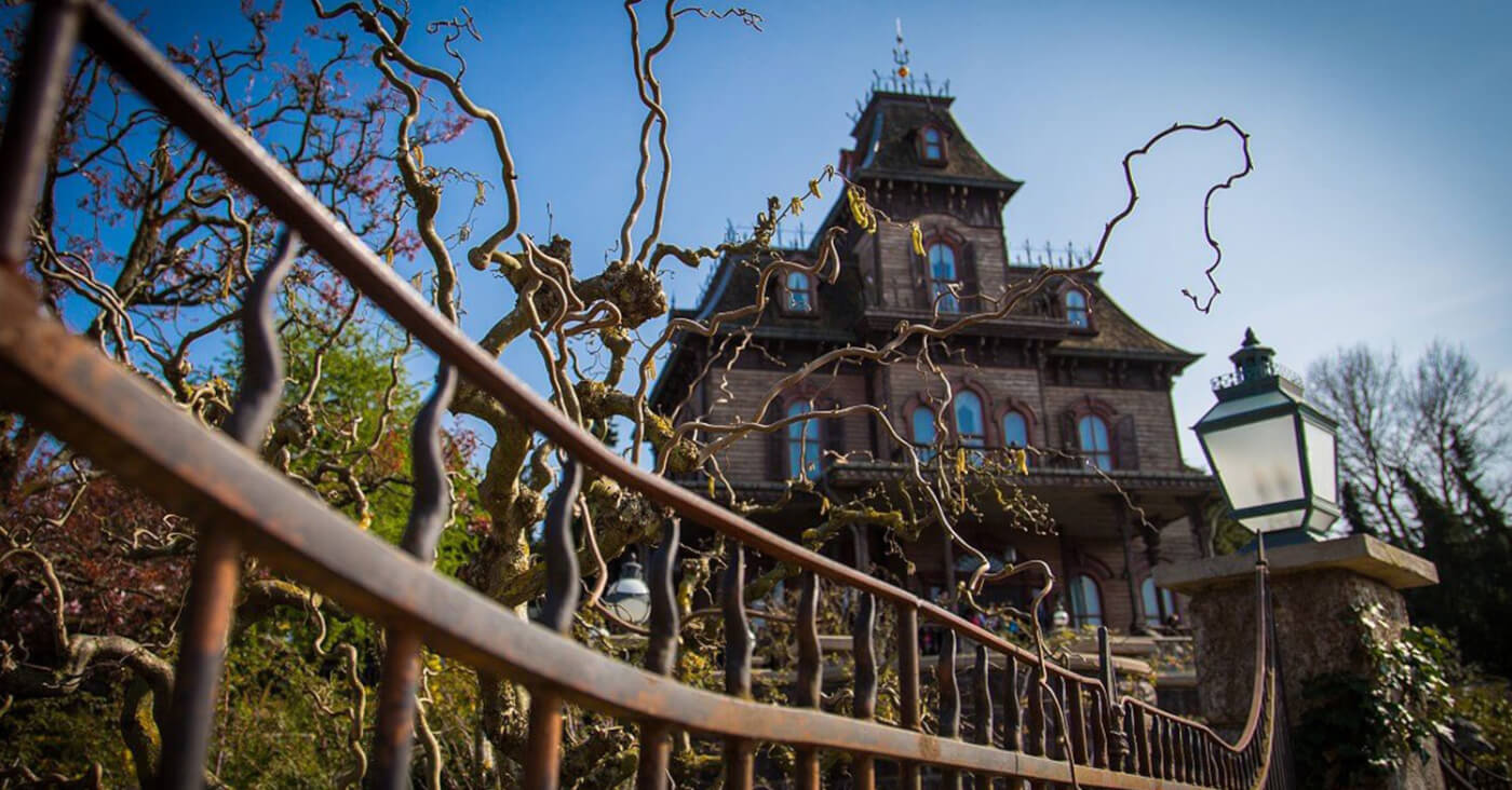 Das Spukhaus Phantom Manor in Disneyland Paris mit einem rostigen Zaun im Vordergrund