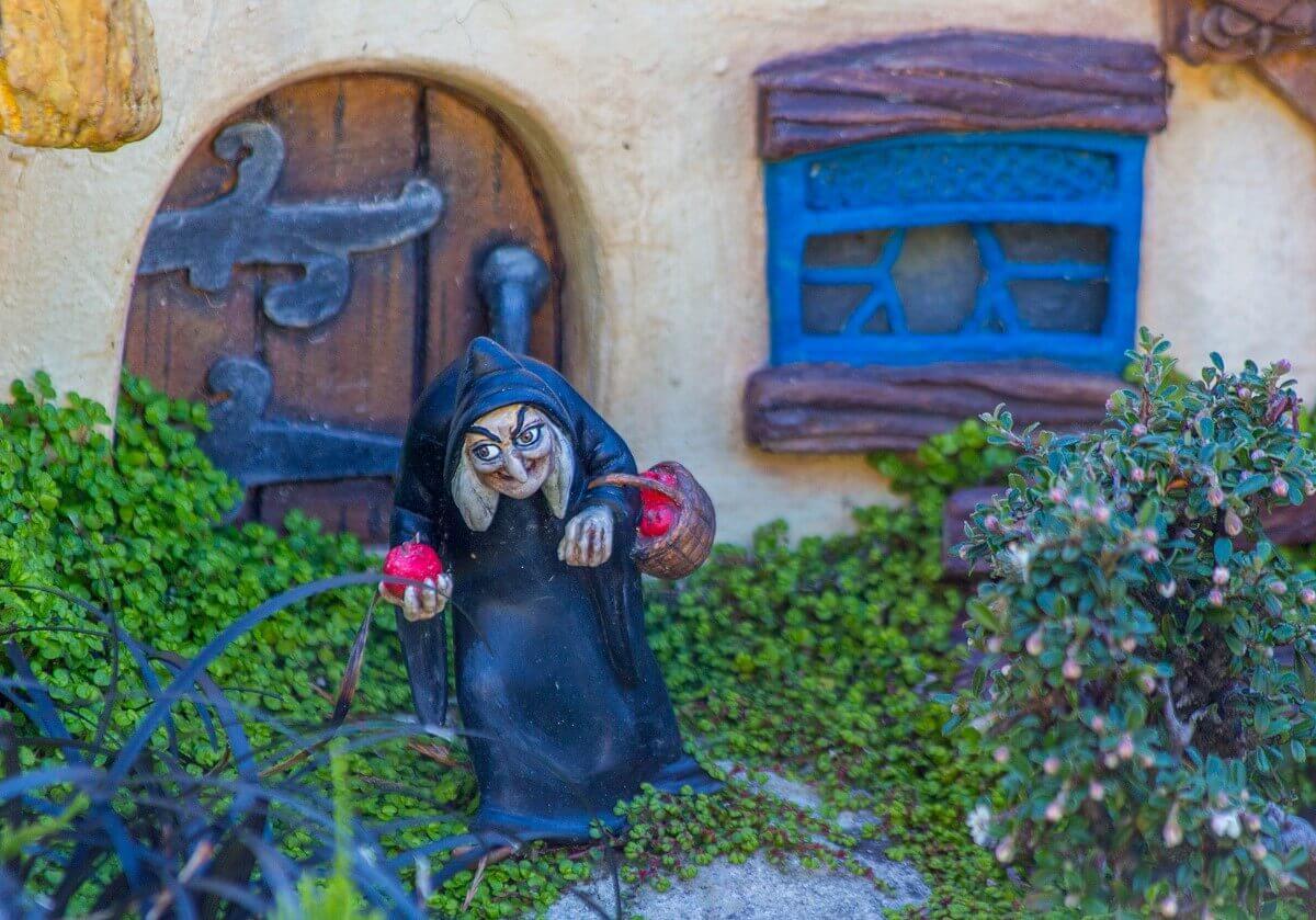 Zu sehen ist die böse Hexe aus Schneewittchen vor dem Haus der sieben Zwerge, hier als Miniatur in der Attraktion Le Pays des Contes de Fées