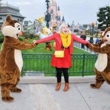 Eine junge Frau steht in einem Gaston-Disneybounding-Outfit zwischen Chip und Chap