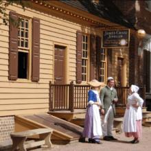Drei Personen stehen im Freilichtmuseum Colonial Williamsburg vor einem Haus