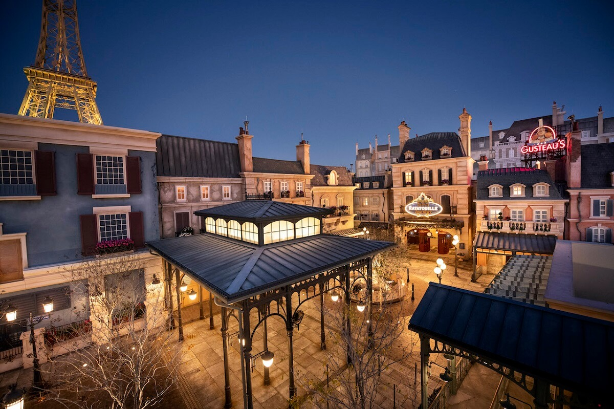 Ein Fotografie bei Nacht zeigt den wunderschön erleuchteten Platz vor der neuen Ratatouille-Attraktion im Frankreich-Pavillon in Epcot
