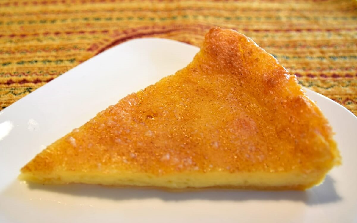 Auf einem kleinen weißen Teller liegt ein Stück der frisch gebackenen Melktert mit Zimt-Zucker-Topping