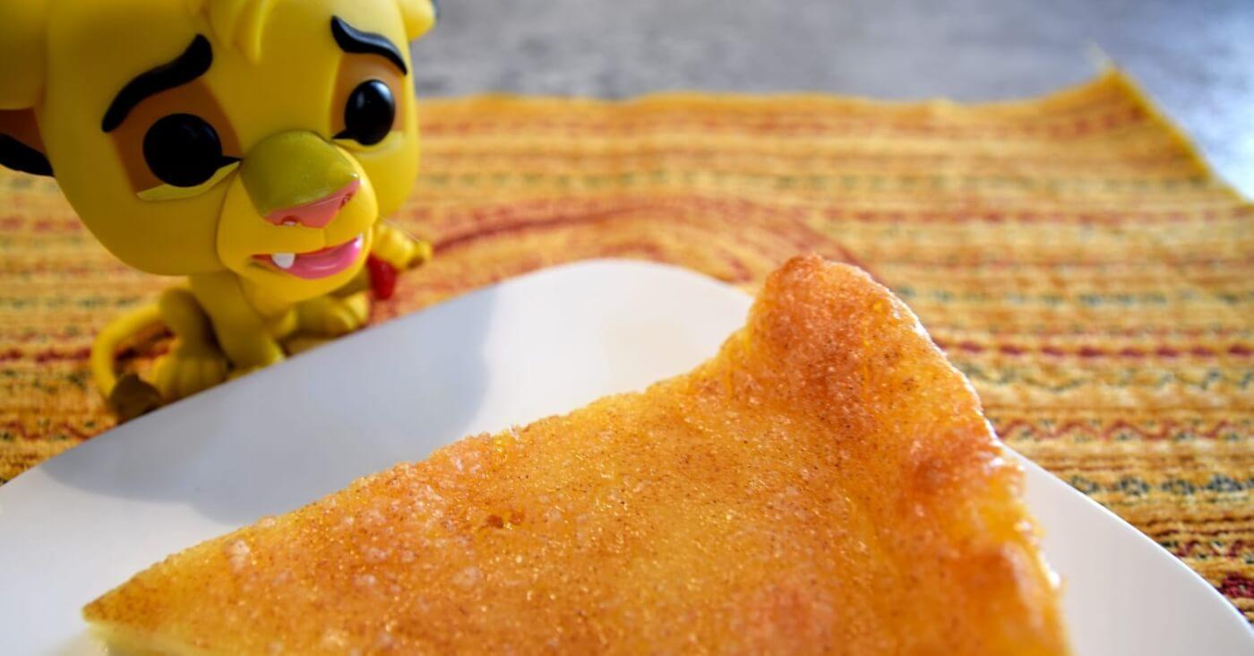 Auf einem Teller liegt ein Stück Melktert, daneben ist eine Simba Funko Pop Figur zu sehen
