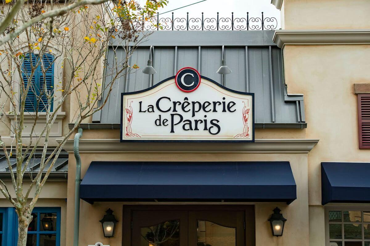 Blick auf die Fassade und das über dem Eingang hängende Schild des neuen Restaurants La Creperie de Paris im Frankreich-Pavillon in Epcot