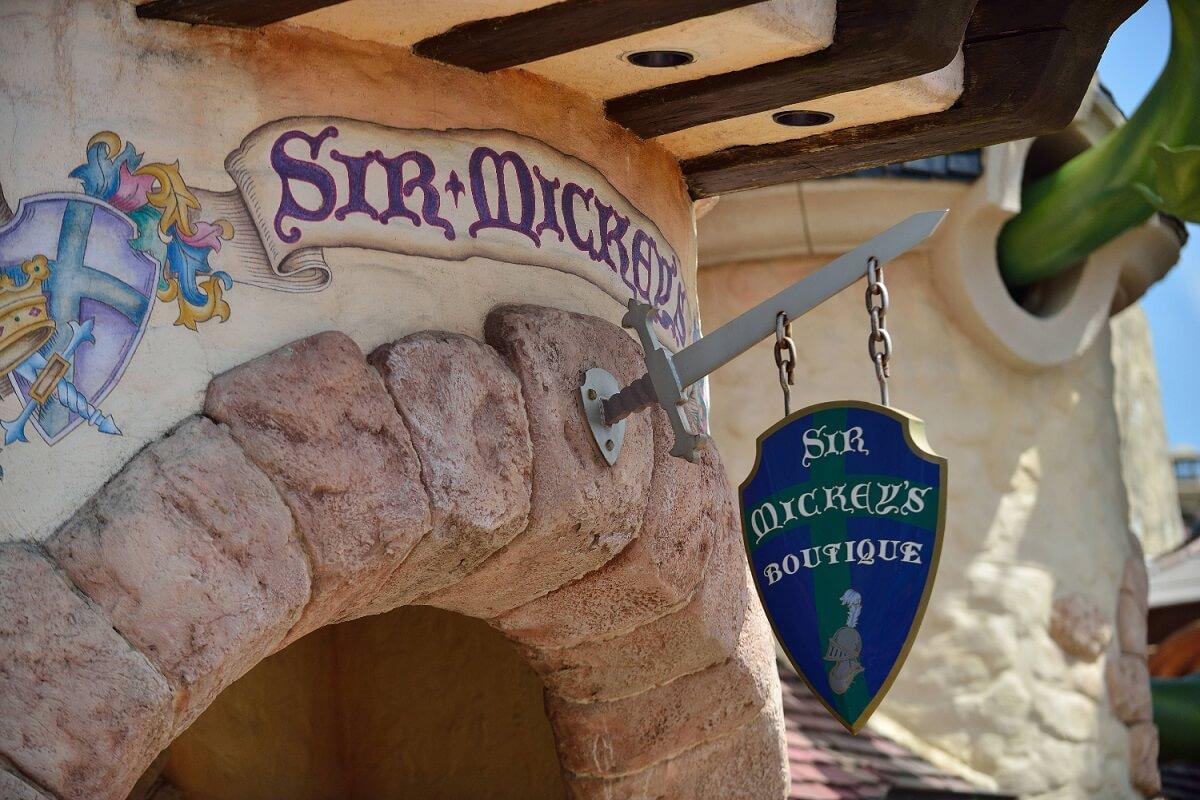 Über einem Eingang zu SIr Mickey's Boutique im Fantasyland hängt ein Schild in Form eines mittelalterlichen Schilds