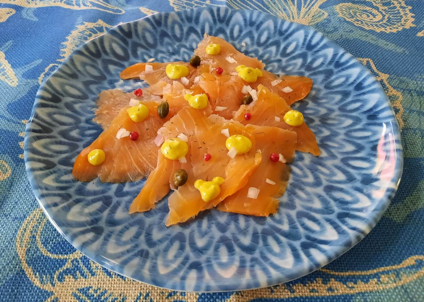 Räucherlachs hübsch angerichtet mit Honig-Senf-Sauce, fein geschnittenen Schalotten, pinkem Pfeffer und Kapern