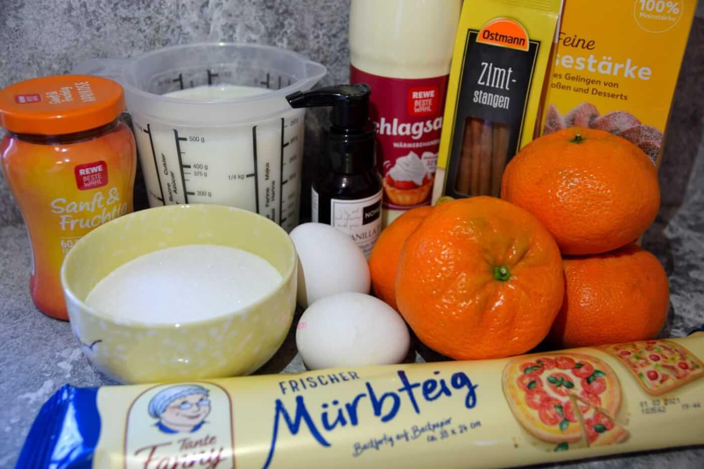 In einer Küche liegen alle für die Melktert benötigten Zutaten wie Mandarinen, Mürbeteig und Sahne