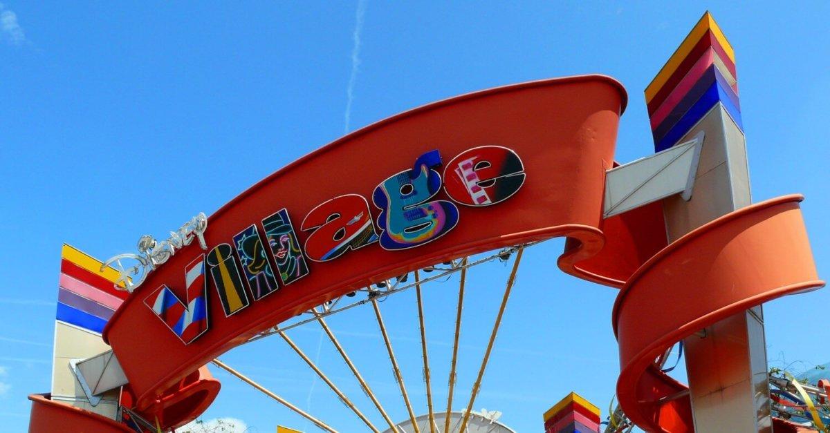 Disney Village Schriftzug auf einem großen roten Bogen, hoch über dem Eingang