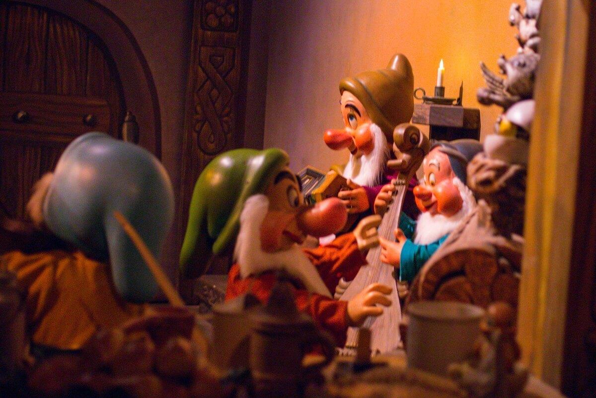 Eine Szene aus der Attraktion zum Film Schneewittchen, in der die Zwerge mit ihren Musikinstrumenten in ihrer Hütte zu sehen sind.