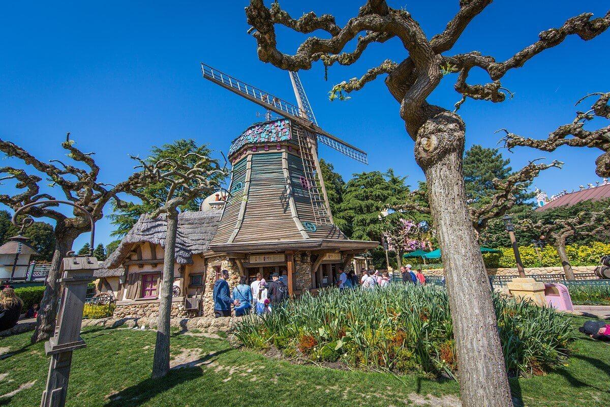 Inmitten einer grünen Fläche ist die alte Windmühle im Fantasyland des Disneyland Paris zu sehen