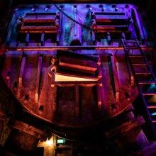 Mystischer Heizkessel blau-rot beleuchtet im Kellergeschoss sieht aus wie eine Maske mit Augen, Nase und Mund.