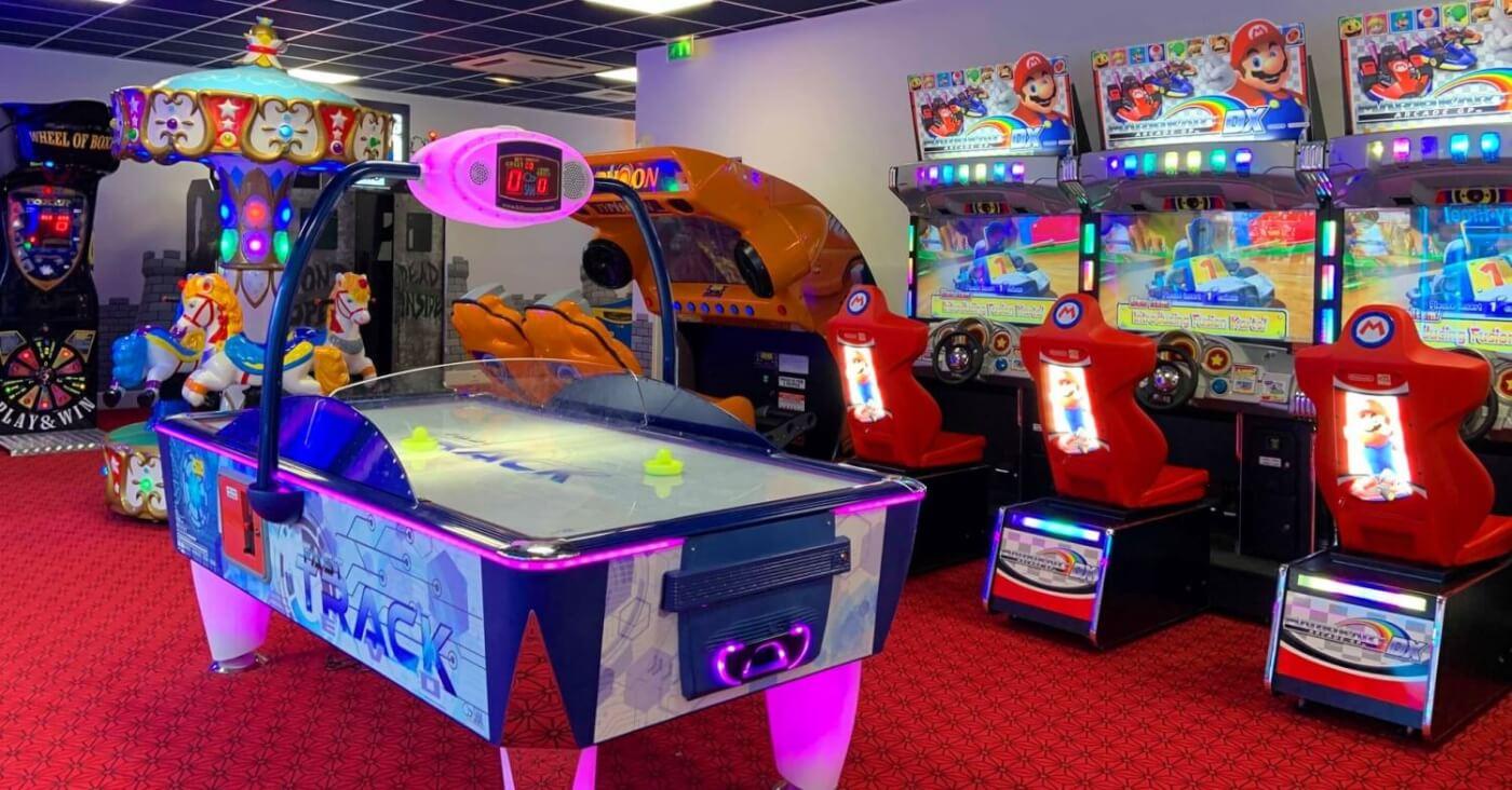 Ein Foto zeigt das Innere einer Video Game Arcade in Disneyland Paris mit verschiedenen Videospiel-Automaten und einem Airhockey-Tisch