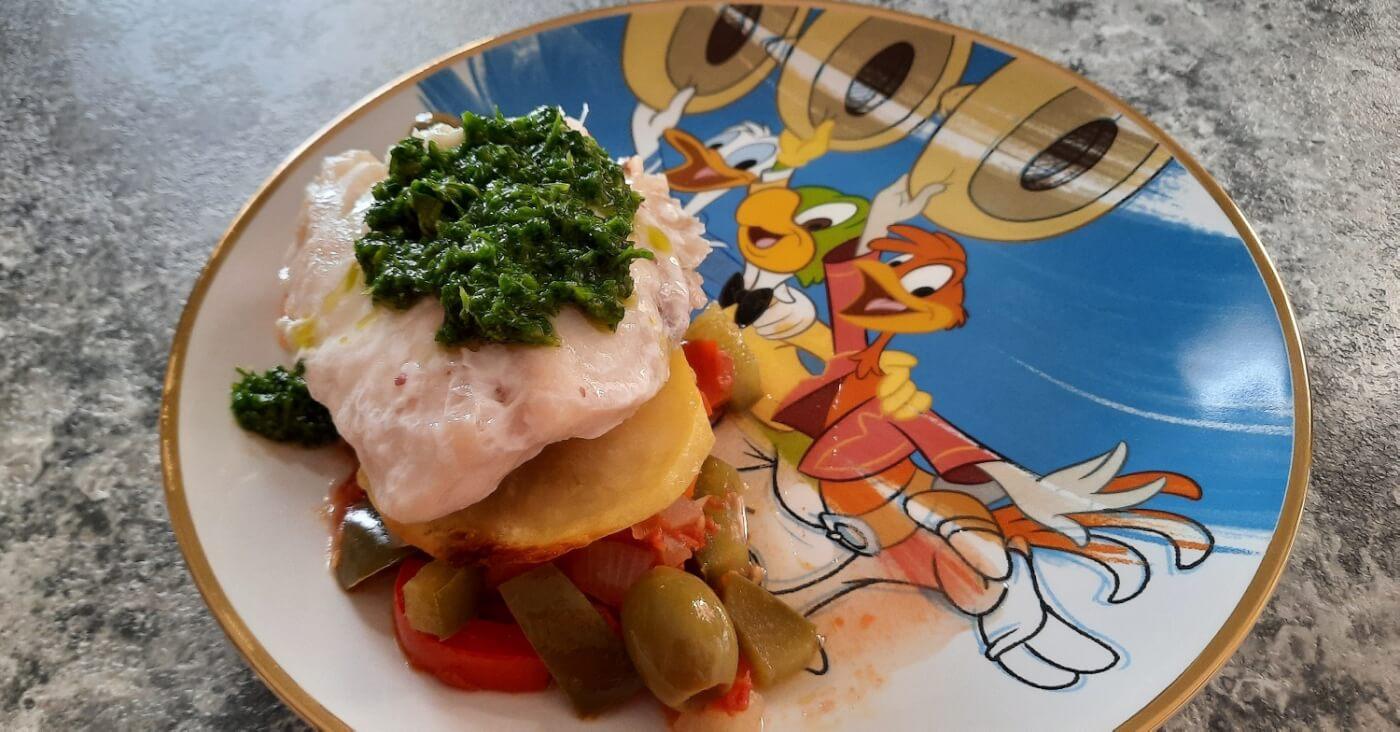 Eine Portion des Pescado a la Veracruzana nach einem Rezept aus dem San Angel Inn Restaurante auf einem Teller mit Drei Caballeros-Motiv