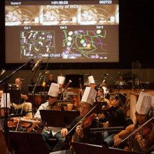 Das Orchester für das Einspielen der Musik sitzt im Tonstudio und trägt während des Spielens Chefkoch-Mützen.