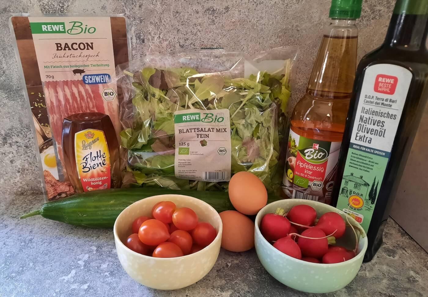 Alle für den Harvest-inspired Garden Salad benötigten Zutaten sind auf einer Küchenarbeitsfläche zu sehen