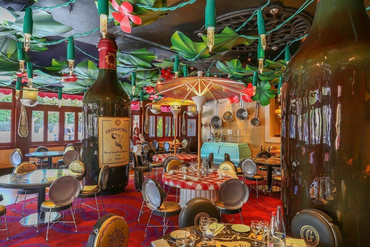 Der Essbereich des Restaurant Chez Rémy mit übergroßen Flaschen als Säulen und Tischen und STühlen aus Flaschendeckeln.
