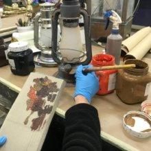 Auf einem Stück Holz sind verschiedenen Farben und werden mit dem Pinsel auf die restaurierte Öllampe aufgetragen
