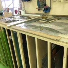 Auf einer Werkbank liegen bemalte Glaselemente in Form einer Seerose