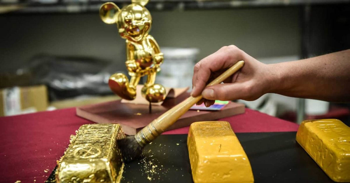 Pinsel vergoldet einen Gipsbarren, im Hintergrund eine goldene Mickey Statue