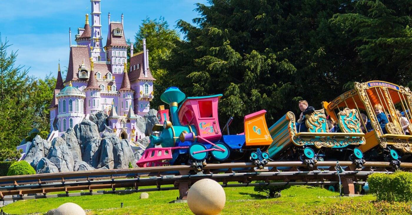 Der Zug Casey Jr. aus der gleichnamigen Attraktion in Disneyland Paris vor dem Schloss des Storybookland.