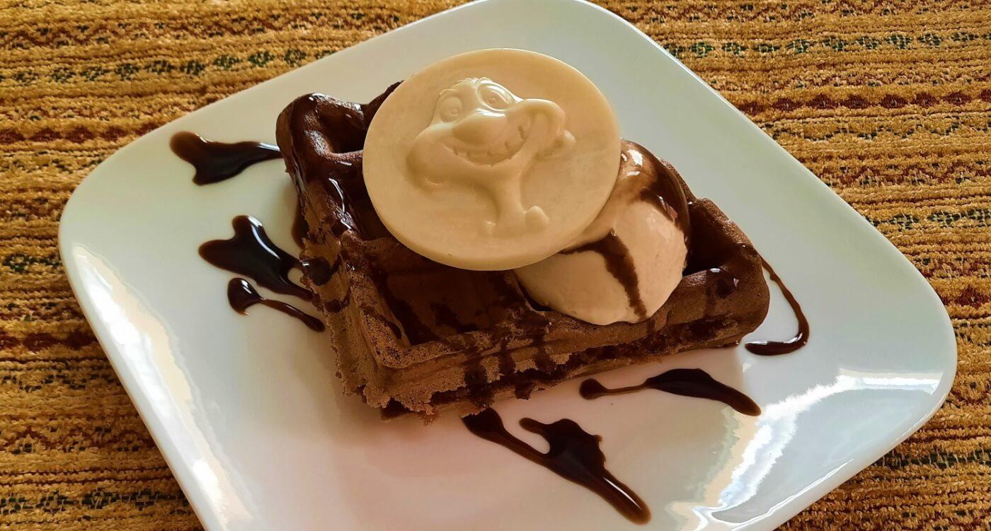 Auf einem kleinen quadratischen weißen Teller liegt eine Schokoladenwaffel mit gefrorener Espresso-Mousse und einem weißem Schokoladentaler mit einer Abbildung von Timon aus Disney's König der Löwen