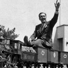 Walt Disney sitzt winkend auf dem Modellzug, der auf seinem Grundstück fährt.