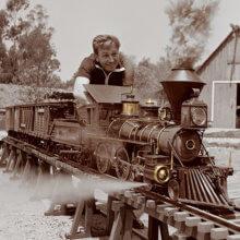 Walt Disney sitzt inmitten seiner aufgebauten Modelleisenbahn.