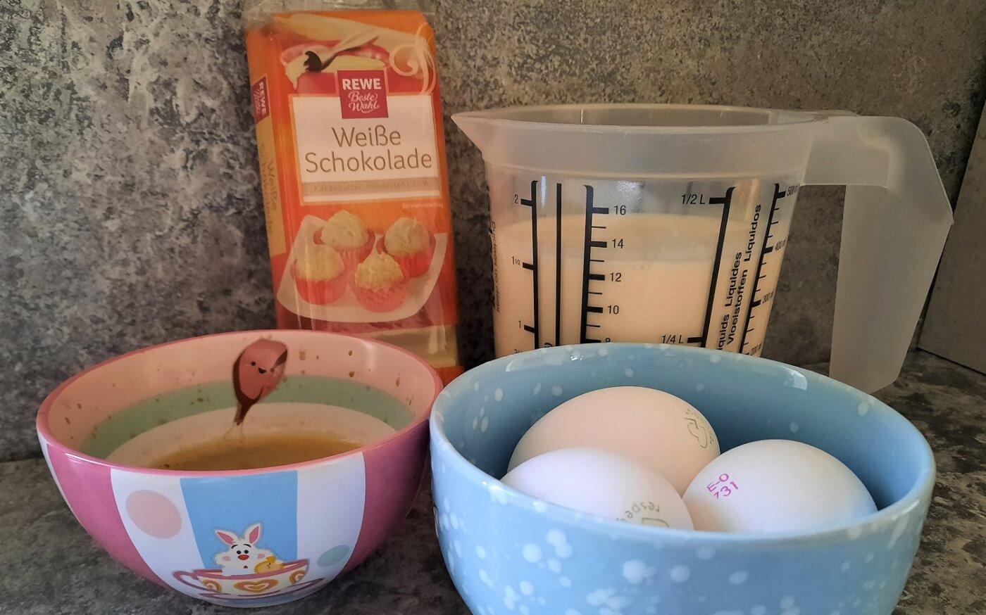 Schlagsahne, weiße Schokolade, Eier und frischer Espresso sind in Gefäßen auf einer Küchenarbeitsfläche sichtbar