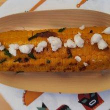 In einer Bambusschale liegt ein gegrillter Maiskolben mit Bröseln von veganem Feta obenauf