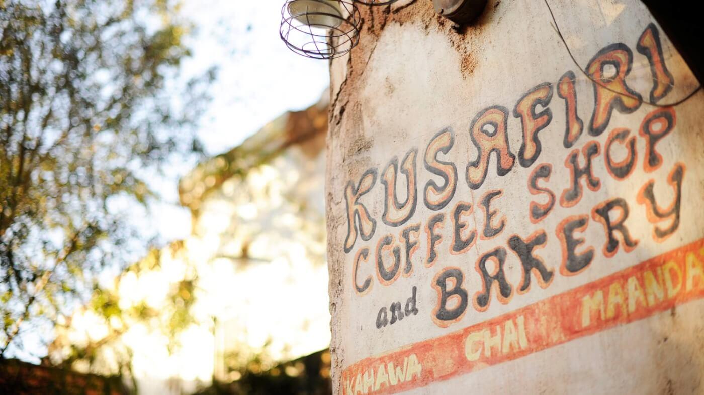 Eine Nahaufnahme der Fassade des Kusafiri Coffee Shop in Disneys Animal Kingdom zeigt den Schriftzug Kusafiri Coffee Shop and Bakery in bunten Lettern