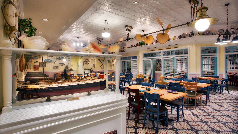 Blick in den Innenraum von Olivia's Café mit vielen Sitzplätzen und maritimem Dekor an Wänden und Decke