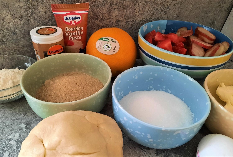 In mehreren Schälchen sind Zucker, Butter, Erdbeeren, Rhabarber und einige andere benötigte Zutaten für einen Pie zu sehen