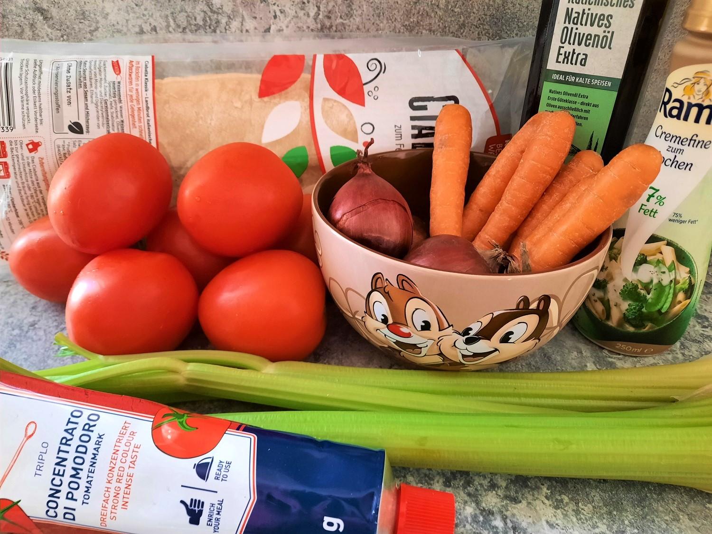 Tomaten, Karotten, Stangensellerie, Zwiebeln und weitere Zutaten für die Tomato Bisque nach Disney World Rezept sind auf einer Küchenarbeitsfläche zu sehen
