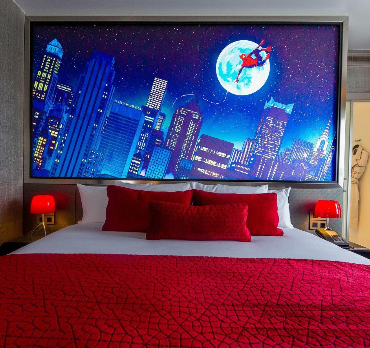 Ein Bett mit rotem Überwurf und roten Kissen, über dem ein großes Bild von Spiderman über den Dächern New Yorks hängt