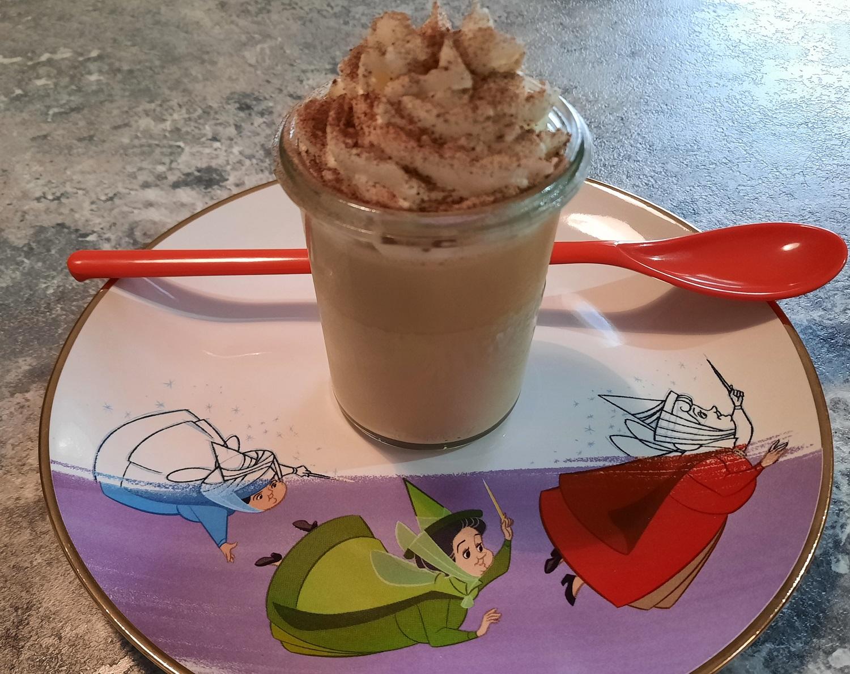Nachtisch in einem Dessertglas mit langem rotem Löffel auf einem Dessertteller mit Disney Motiv
