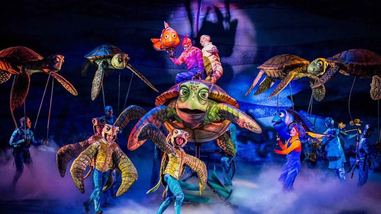 Auf der Bühne von Finding Nemo The Musical sind Tänzer und Puppenspieler in Kostümen zu sehen