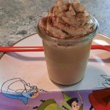 Ein Dessertglas mit Kaffee-Karamell-Dessert auf einem Teller mit Abbildung der drei Feen aus Dornröschen
