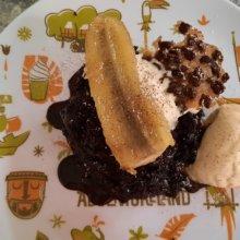 Ein Schokoküchlein mit Schokoladensauce, karamellisierter Banane, Vanilleeis, Sahne und Cacao Nib Tuile auf einem Teller mit Adventurelandmotiv