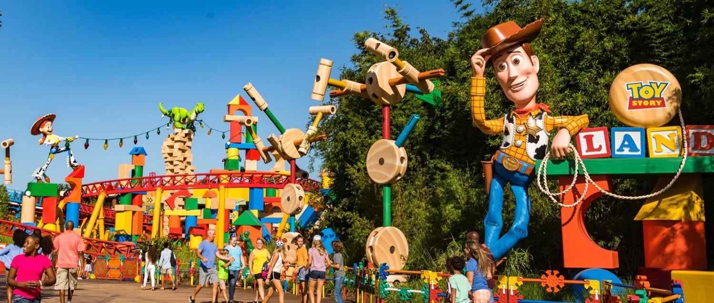 Eingang zum Toy Story Land mit einer großen Woody-Figur rechts vorne und einer Achterbahn im Hintergrund