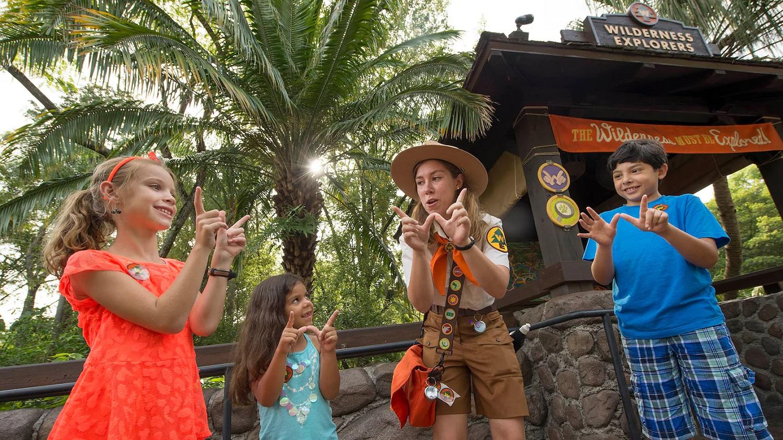 Ein weiblicher Cast Member im Wilderness Explorers Kostüm zeigt drei Kindern, wie sie mit ihren Händen ein W formen können